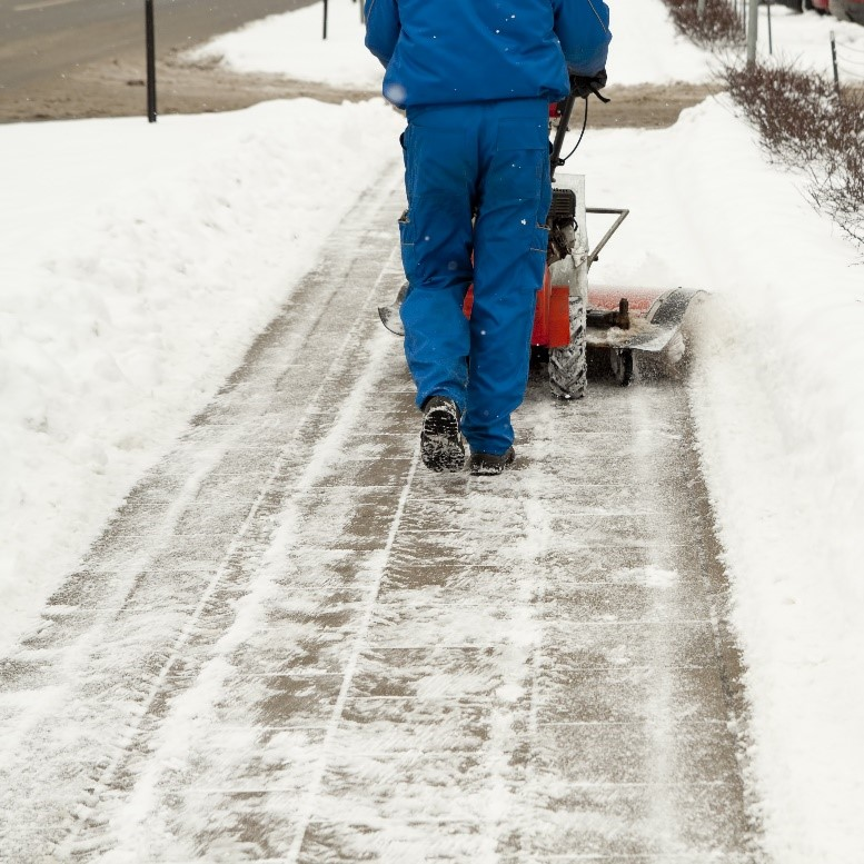 Person performing snow removal on a walkway