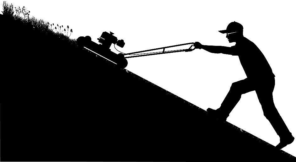 Silhouette of man using walk-behind mower on a steep hill